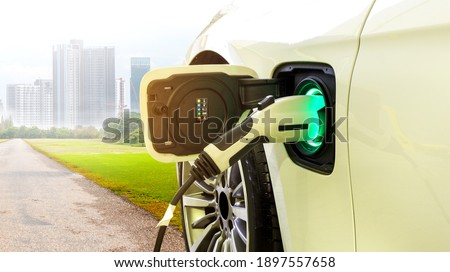 EV Car or Electric car at charging station with the power cable supply plugged in on Green environment with a long road leading to the city of the future.