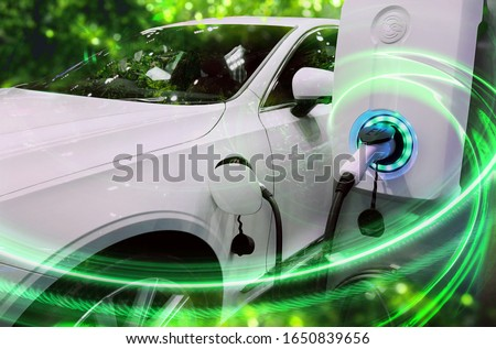 EV Car or Electric vehicle at charging station with the power cable supply plugged in on blurred nature with green enegy power effect. Eco-friendly sustainable energy concept.