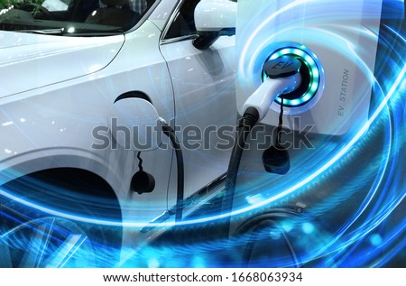 EV Car or Electric vehicle at charging station with the power cable supply plugged in on blurred nature with blue enegy power effect. Eco-friendly sustainable energy concept.