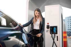 EV charging station, eco fuel concept. Portrait of pretty young girl inserting charging plug into her modern electric car for refueling at city station