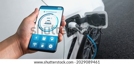 EV charging station for electric car with mobile app display charger status . The electric power is produced from sustainable resources to supply to charger station in order to reduce CO2 emission . Stockfoto ©
