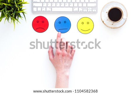 Evaluate customer service. Hand point emoji smiling, neutral, sad face on work desk on white background top view copy space #1104582368