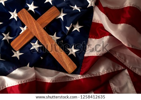 Evangelical America, christianity, born again christian and fundamentalist religious right concept with close up on a wooden cross or crucifix on the american flag with dramatic light and moody tone Stock photo ©