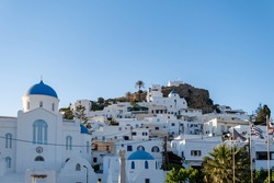Evangelismos Cathedral Orthodox church and chapel at Ios Nios island Chora Cyclades Greece. Traditional stonewall buildings in white and blue color background. Religious destination blue sky sunny day