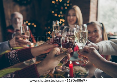 Eve family gathering meeting dream wish concept. Cropped wineglass, cheerful gray-haired grandparents, grandchildren, daughter sitting at table, house party, fun joy navidad hands hold glass