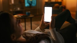 Evening at Home: Young Woman Resting on a Couch using with White Mock-up Screen Smartphone. Girl Using Chroma Key Mobile Phone, Internet Browsing, Posting on Social Networks.
