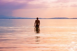 evening at lake chiemsee. man walking into the water for swimming.