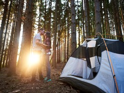 Evening camping at sunset in the forest. Young romantic man and woman kissing near white tourist tent. On the background beautiful view of setting sun. Tourism adventure active lifestyle concept