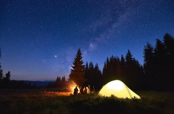 Evening camping near fire, spruce forest and mountains on background. Group of friends having a rest near bright bonfire. People sitting near tourist tent under night sky full of stars and Milky way.