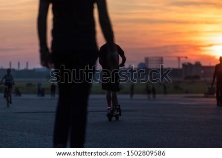 evening city sundown with an e-scooter rider #1502809586