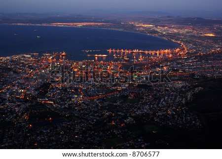 Evening cityscape of town with ocean bay and mountains from bird view
