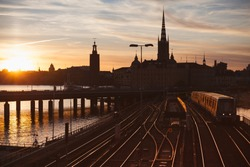 Evening cityscape with subway train crossing the bridge of Gamla Stan, Stockholm, Sweden