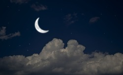 Evening crescent in the cloudy sky