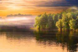 Evening Dnieper river covered with haze. Amazing sunset view, water scape with dramatic yellow sky and beautifully lit trees.