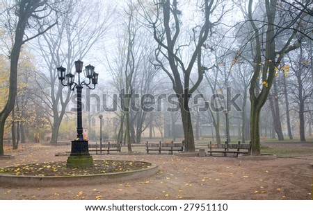Evening dull foggy autumn city park with lamp and benches