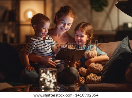 evening family reading. mother reads children a book before going to bed