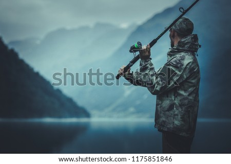Evening Fly Fishing Time. Caucasian Fisherman with Fishing Rod on the Glacial Lake Shore.
