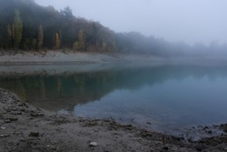 Evening fog on the lake. Grey autumn landscape. Mystical view of a mountain lake and in a blue haze. Silence and sadness. Sad autumn background. Lake with reflections.