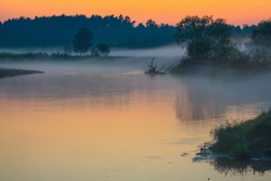 Evening fog under the forest river at the sunset