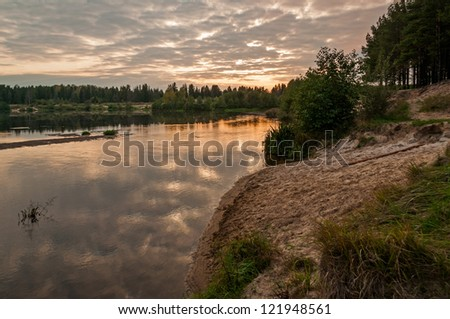 Evening glow of cloudy sky over river valley with sunset reflection in water