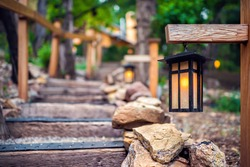 Evening illuminated hanging lantern lamp light on wooden pole post in Japanese garden with steps stairs and green forest foliage by railing background in Japan