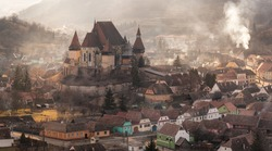 Evening In Biertan,Heart Of Transylvania,One Of Most Famous Four Ancient Fortification Churches Of Romania.Val-Themed Inns And Pastel-Coloured Houses With Dilapidated Tiled Roofs Surround The Fortress