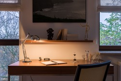 Evening in home office room with windows, simple wooden desk with many stuff and light on