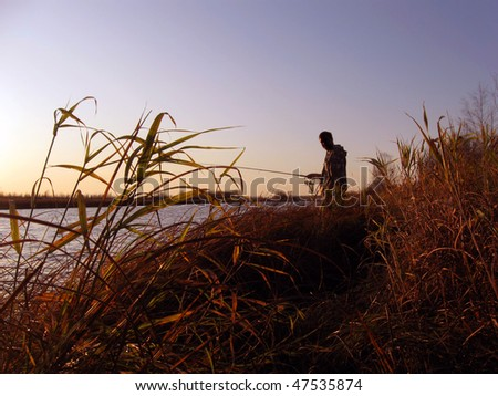 Evening landscape of lake with a silhouette  fisherman