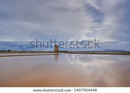 Evening landscape picture of ponds or saltpans in traditional salt production in Trapani in island Sicily during the sunset with cloudy sky and calm sea. Riserva naturale integrale Saline di Trapani.
