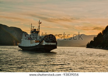 Evening landscape with the ferry which is swimming up to a mooring