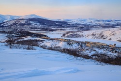 Evening landscape with the town among the mountains. Top view of the northern city. Cold winter weather. Hills covered with snow. City of Magadan, Magadan Region, Far East of Russia. Siberia.