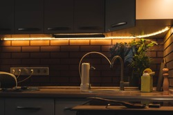 Evening life in a country house in the kitchen with a pleasant warm lighting. Modern interior compact kitchen. LED strip with base. Portable drinking water filter with replaceable cartridges.