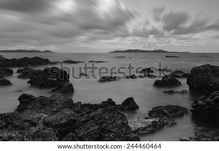 Evening light sunset sea waves splashing rocks black and white tone.