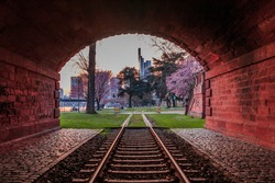 Evening mood in Frankfurt. Historic tunnel with old railroad track. Trees with flowers in the park and meadow. Skyscrapers from the financial district in the background