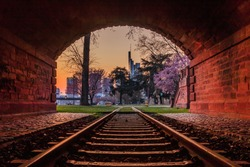 Evening mood in Frankfurt with the skyline of the financial district. Old train track with historical tunnel on the bank of the river Main and park with trees and blossoms for spring.