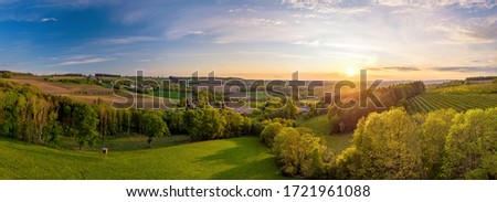 Evening mood over an Upper Austrian cultural landscape in spring with trees and fields in the foreground ストックフォト ©