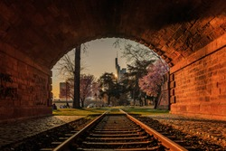 Evening mood with sunset in Frankfurt. Old tunnel with railroad track and park with trees and flowers. Skyscrapers of the skyline in the background of the financial district