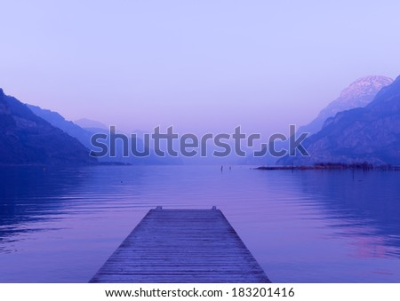 Evening on the lake in Switzerland. Water and mountains painted in pink and purple colors