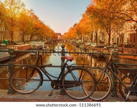 Evening over beautiful Amsterdam canals in autumn. Bicycles parked at the bridges in the foreground