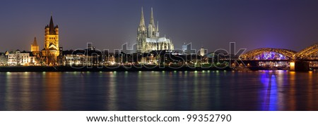 Evening panorama of Cologne with Great St. Martin Church, Cologne Cathedral and Hohenzollern Bridge from bank of the Rhine river, Germany