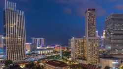 Evening panorama with Marina Bay area and illuminated skyscrapers city skyline aerial day to night transition view. The tower shape building at the North bridge road with traffic in Singapore.
