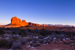 evening photograph with incredible red rock features and the La Sal Mountains in the background