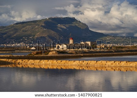 Evening picture of Watermill used like water pump in traditional salt production in Trapani in island Sicily, with mountain and city Erice in background. Riserva naturale integrale Saline di Trapani.