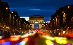 Evening rush-hour on Champs Elysee with the view of illuminated Arc de Triomphe in Paris, France