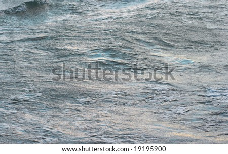 Evening sea waving surface with blue (sky) reflections and yellow (evening sun)