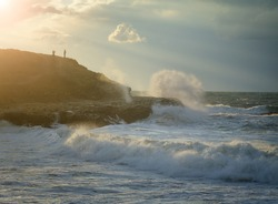 Evening seascape . Storm in ocean with big windy waves. Silhouettes of a peoples on a rock. Nature composition on a background blue sky with clouds sunset.