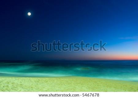 evening seascape with sandy beach, calm ocean and full moon on blue sunset sky