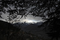 Evening silhouettes of pine trees against the background of an Indian mountain village at the foot of mountain peaks.