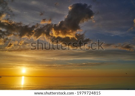 Evening sky with dramatic clouds over the sea. Dramatic sunset over the sea.