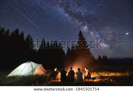 Evening summer camping, spruce forest on background, sky with falling stars and milky way. Group of five friends sitting together around campfire in mountains, enjoying fresh air near illuminated tent